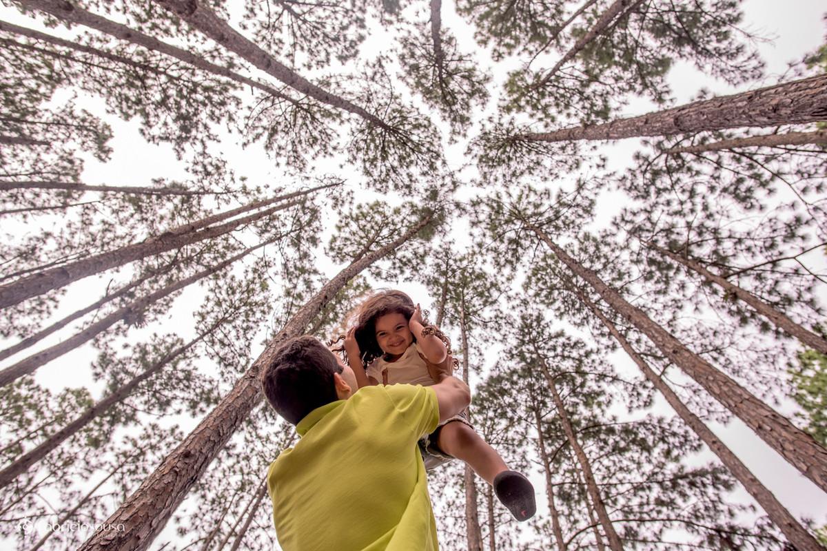 Paizão joga a filha pra cima em meio às árvores