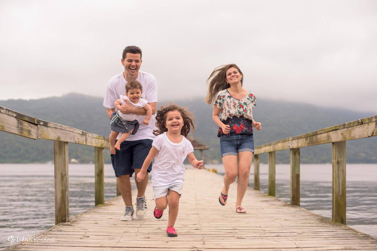 Família correndo pelo trapiche de madeira
