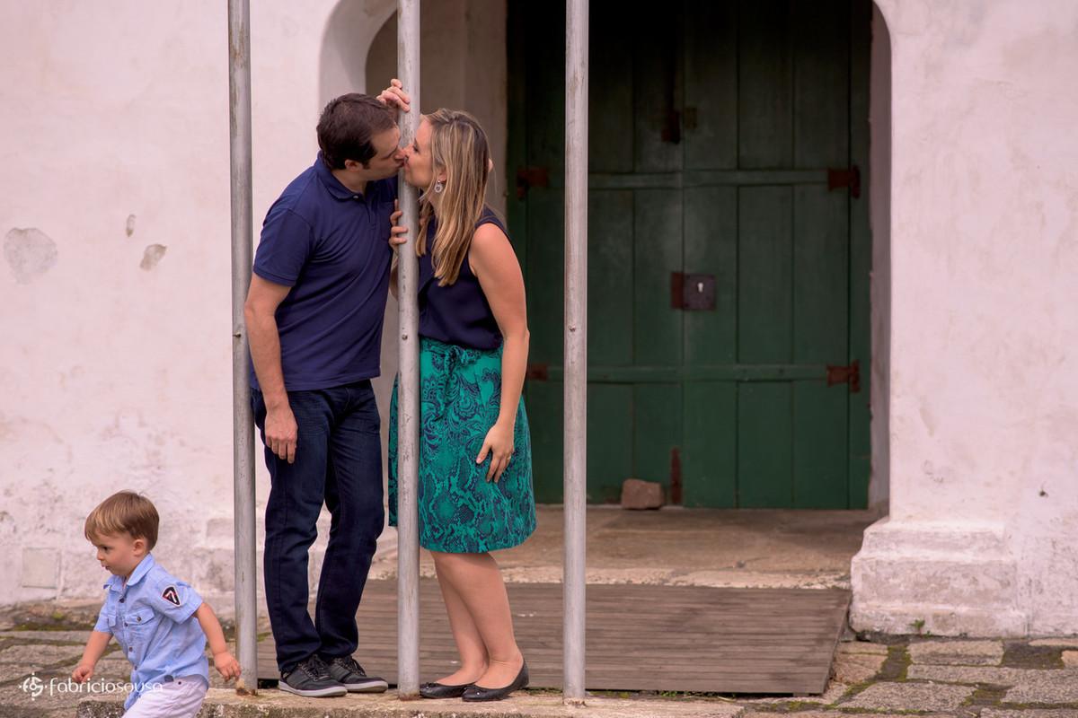 casal se beija e criança corre