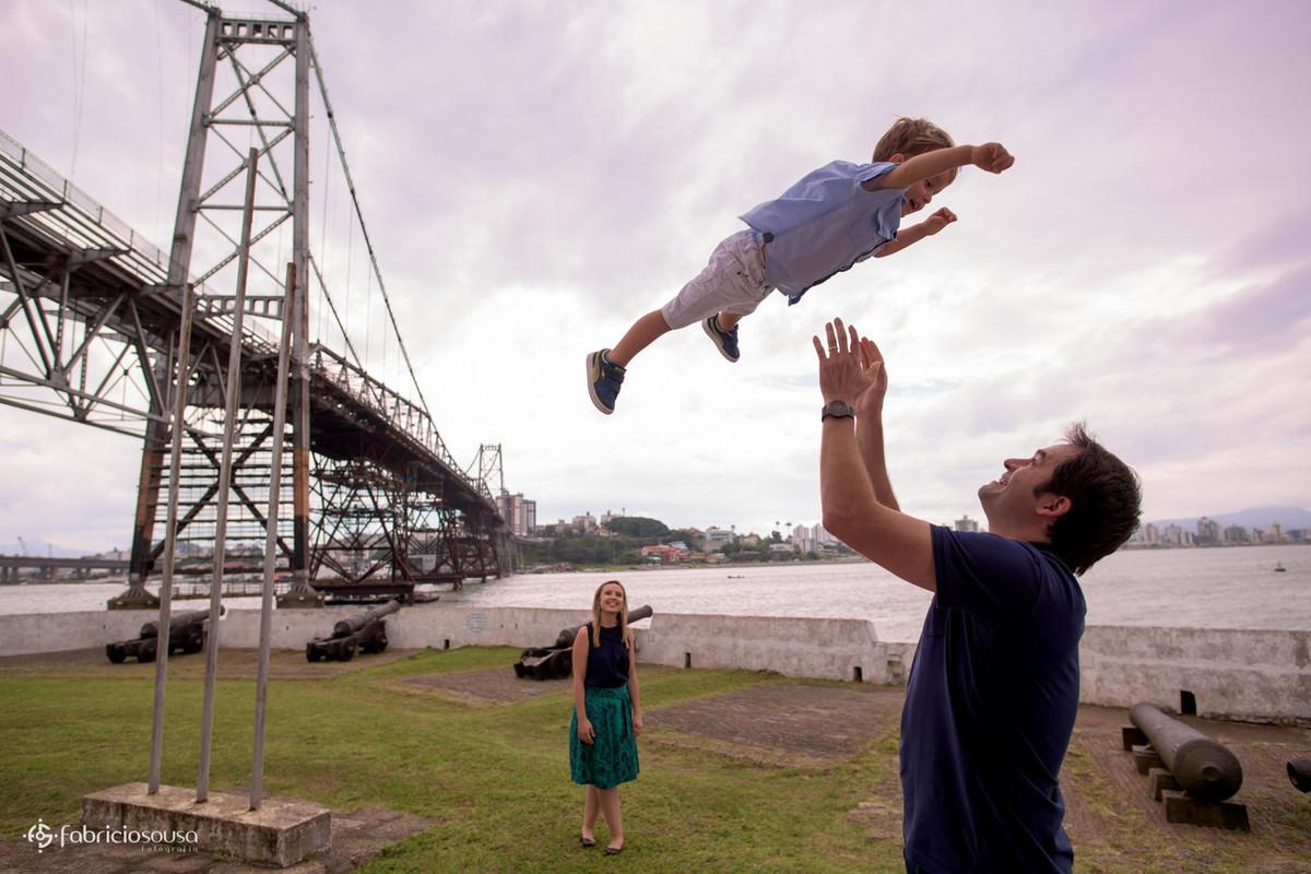 mãe assiste pai jogar filho pro ar com a ponte Hercilio Luz de fundo