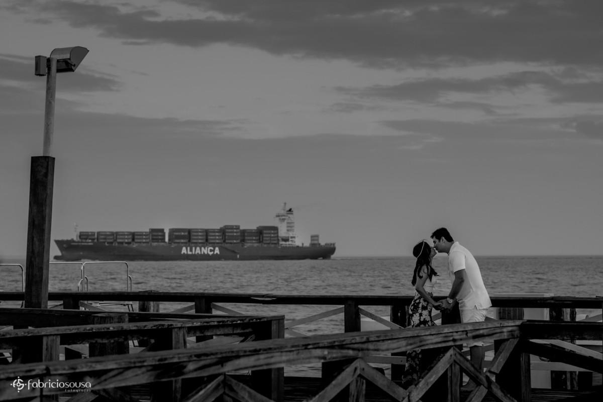 beijo do casal no trapiche com navio aliança no fundo