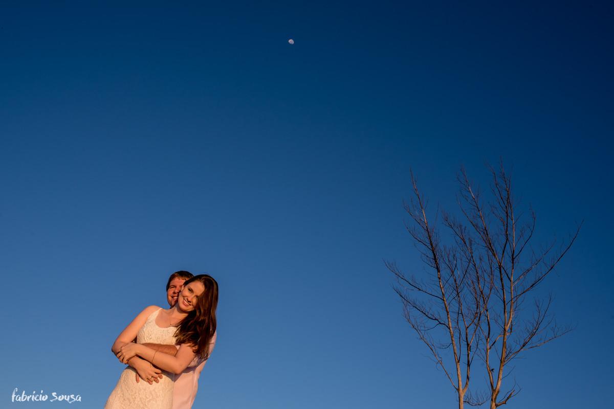 casal agarrado com céu azul e árvore do outono