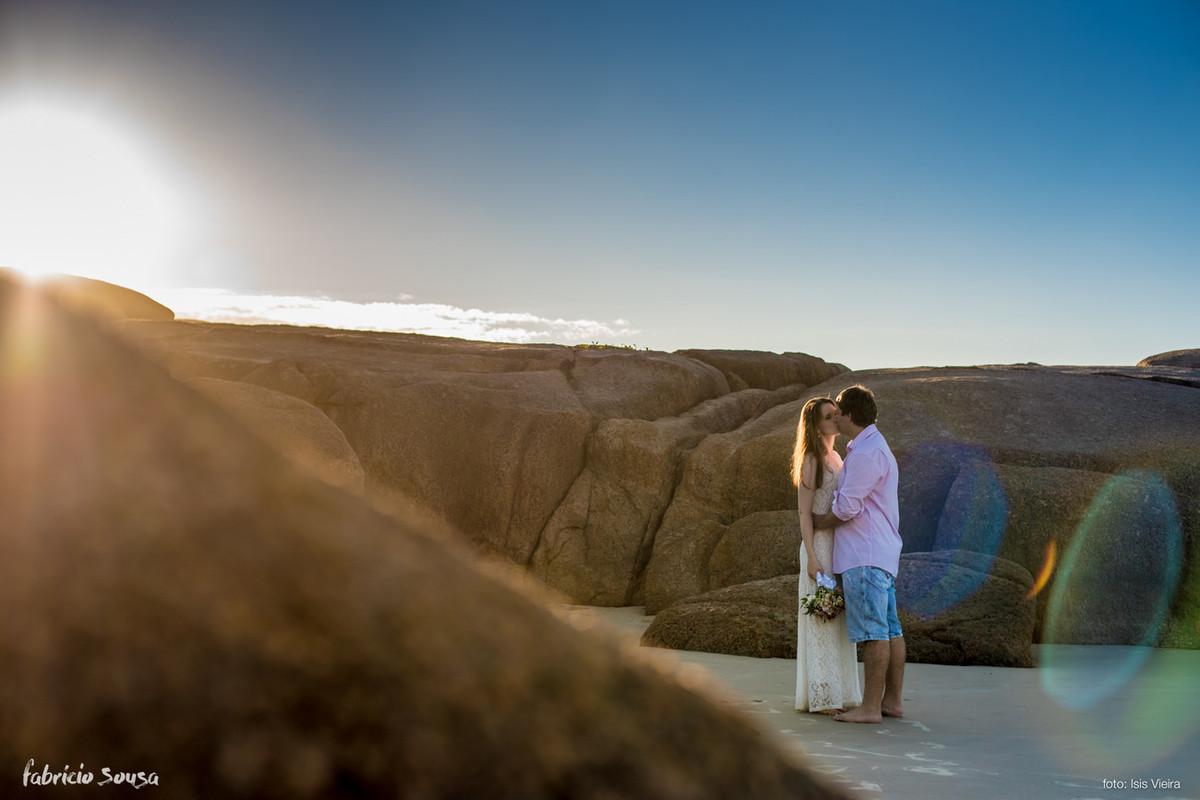 o beijo no canto da praia em meio às pedras