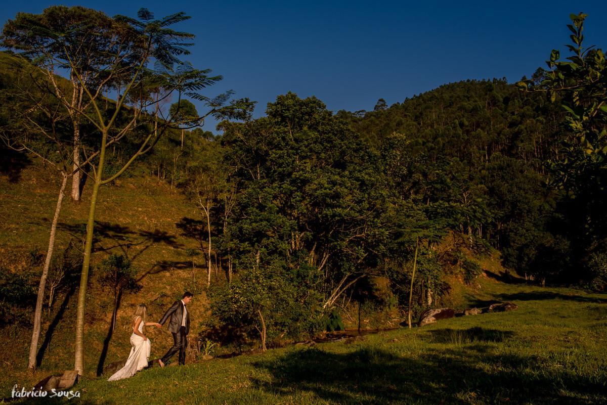 noivos caminham no interior na beira do rio com céu azul de final de tarde