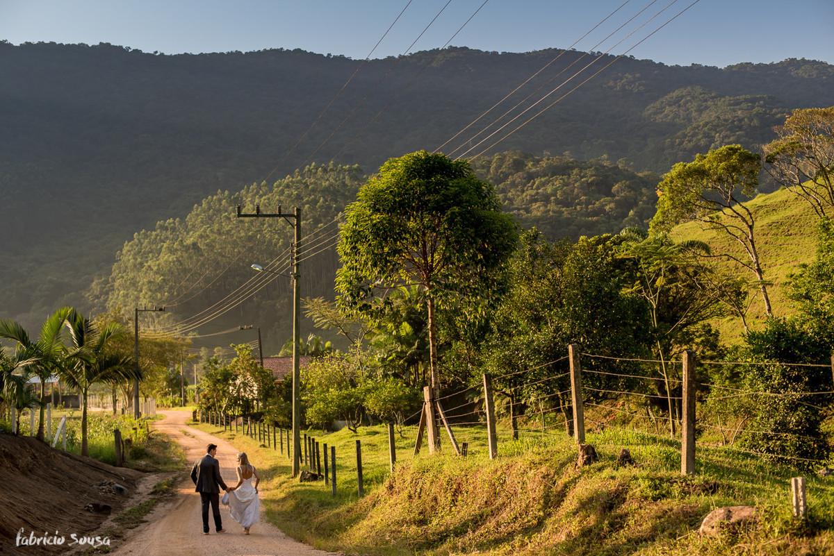 noivos caminham em estrada de chão em ensaio trash the dress