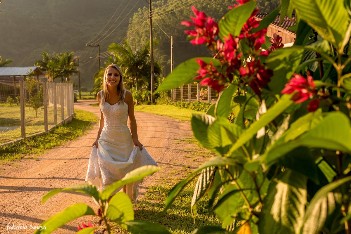 noiva radiante na estrada de terra com flores vermelhas e sol de final de tarde
