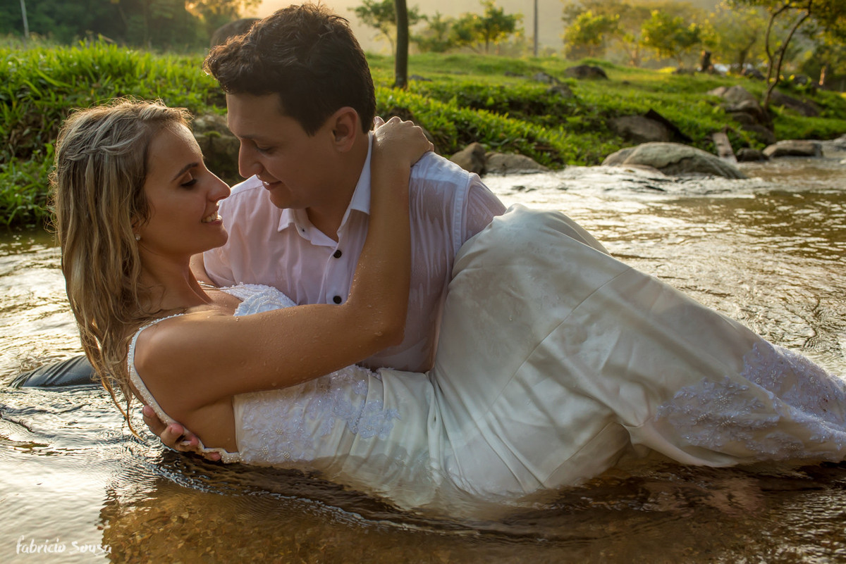 noivos se beijam dentro do rio em ensaio pos-casamento
