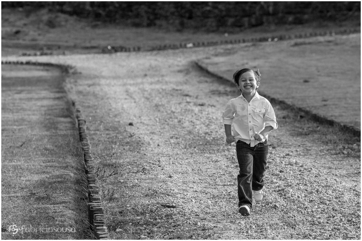 Menino corre feliz e sorridente por caminho de terra e grama
