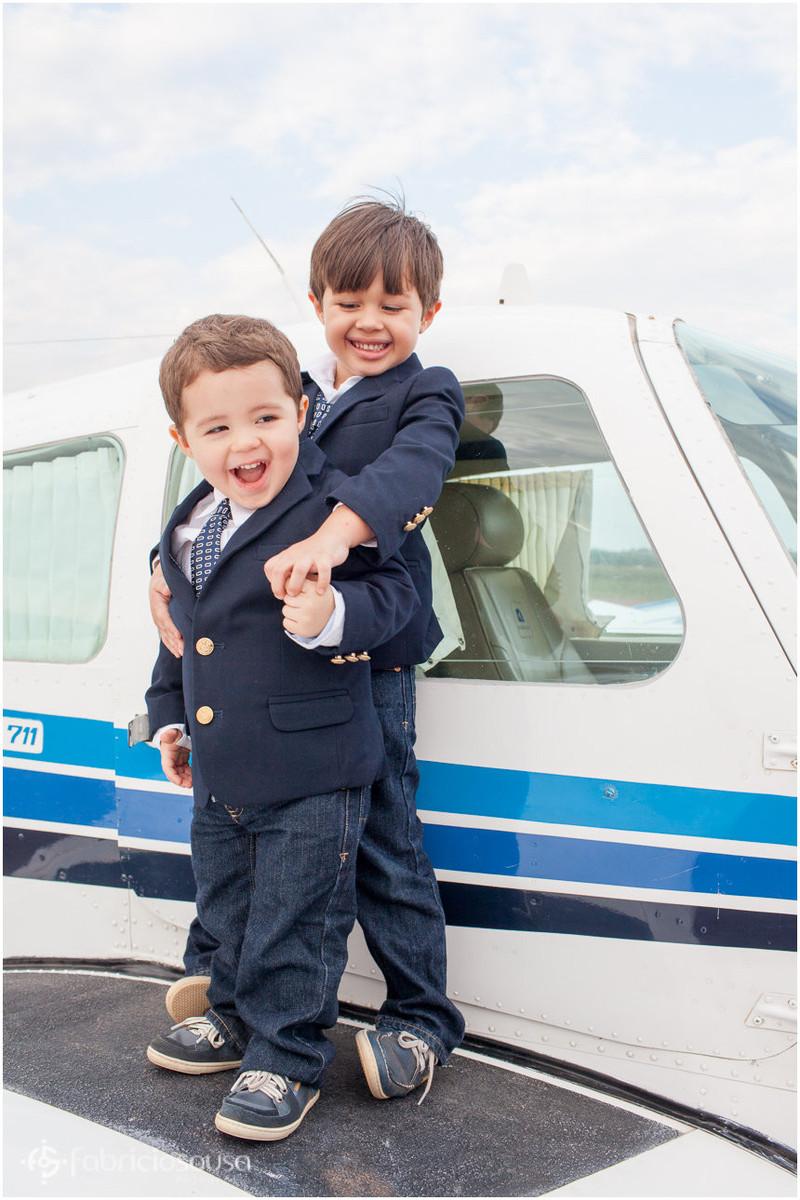Pequenos irmãos abraçados em cima da asa do avião