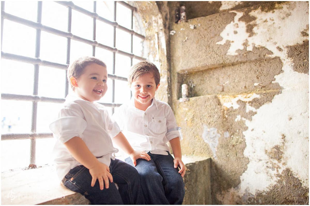 Meninos irmãos sorriem em frente à janela antiga