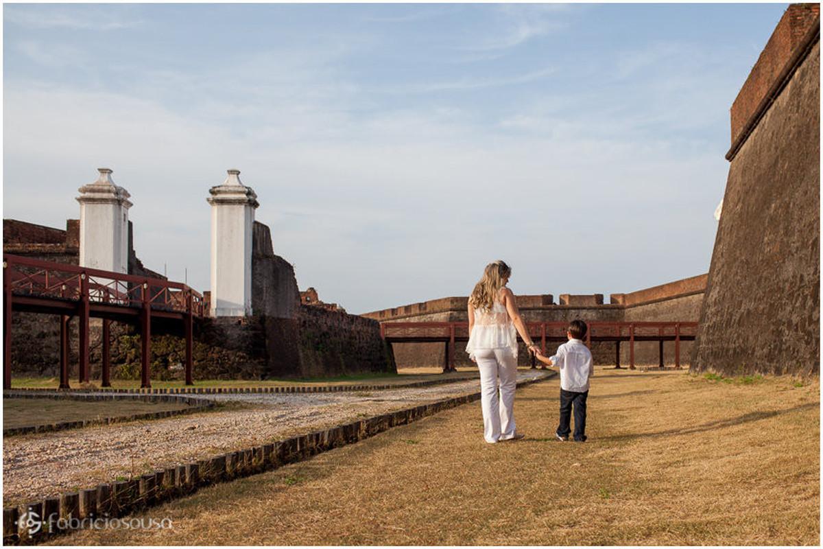 Mae grávida caminha de mão dada com filho na Fortaleza de Macapá
