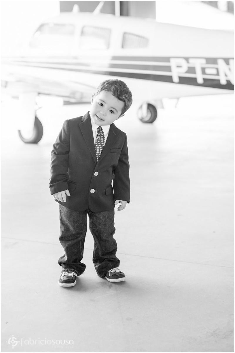 Criança pequena de terno e gravata em hangar perto do avião