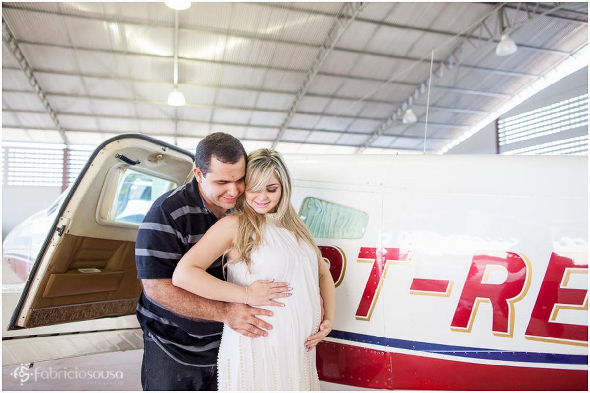 Casal envolve carinhosamente a barriga da mae no hangar