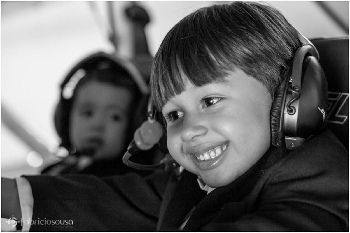 Irmãos pequenos utilizam os head sets do avião p