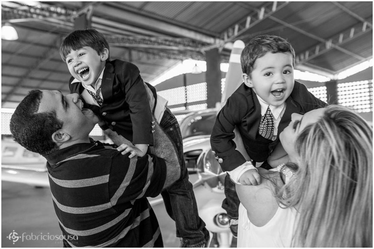 Pai e mãe erguem seus filhos para cima black and white