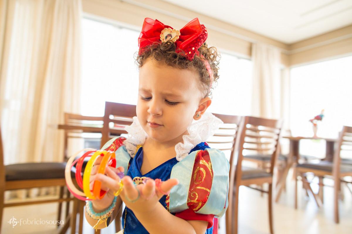 Menina pequena com argolas na mão