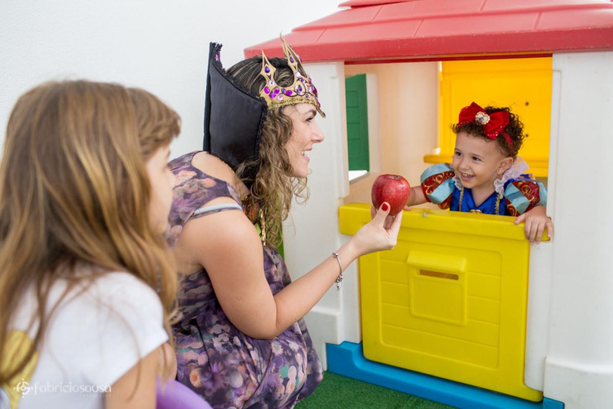 """Mulher vestida de """"bruxa"""" oferecendo a maçã para a criança"""