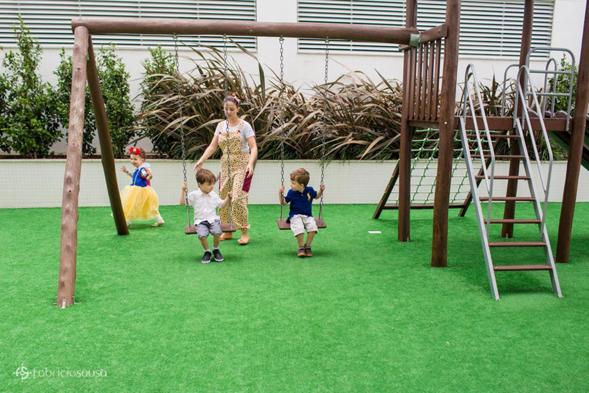 Crianças no balanço do parquinho infantil do prédio