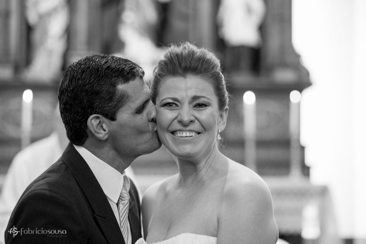 Noivo beija noiva em preto e branco