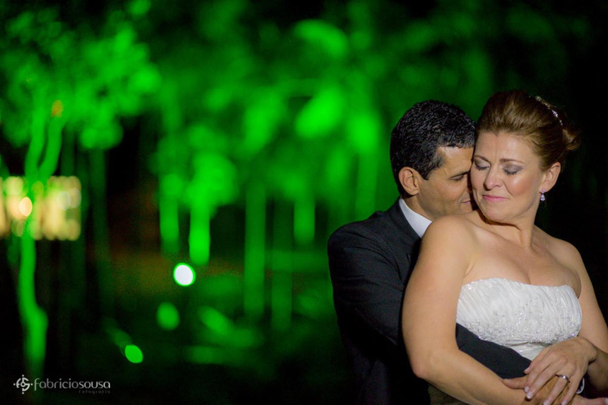 Noivo abraça noiva carinhosamente em sessão fotográfica