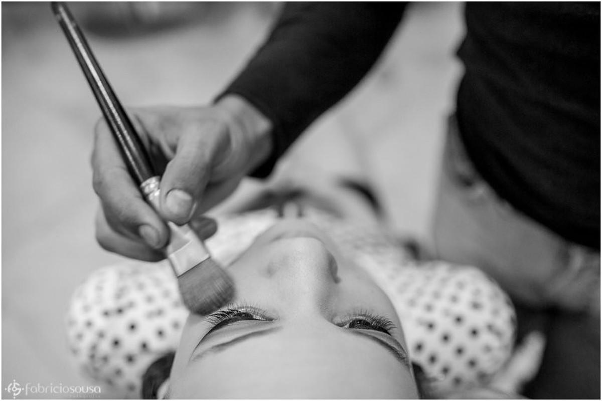 Maquiadora pincelando o rosto da debutante