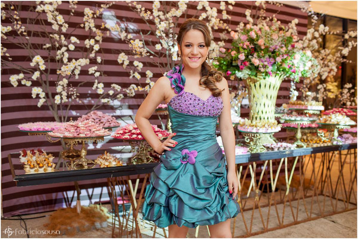 Késsia Rocha posa em frente à mesa de doces