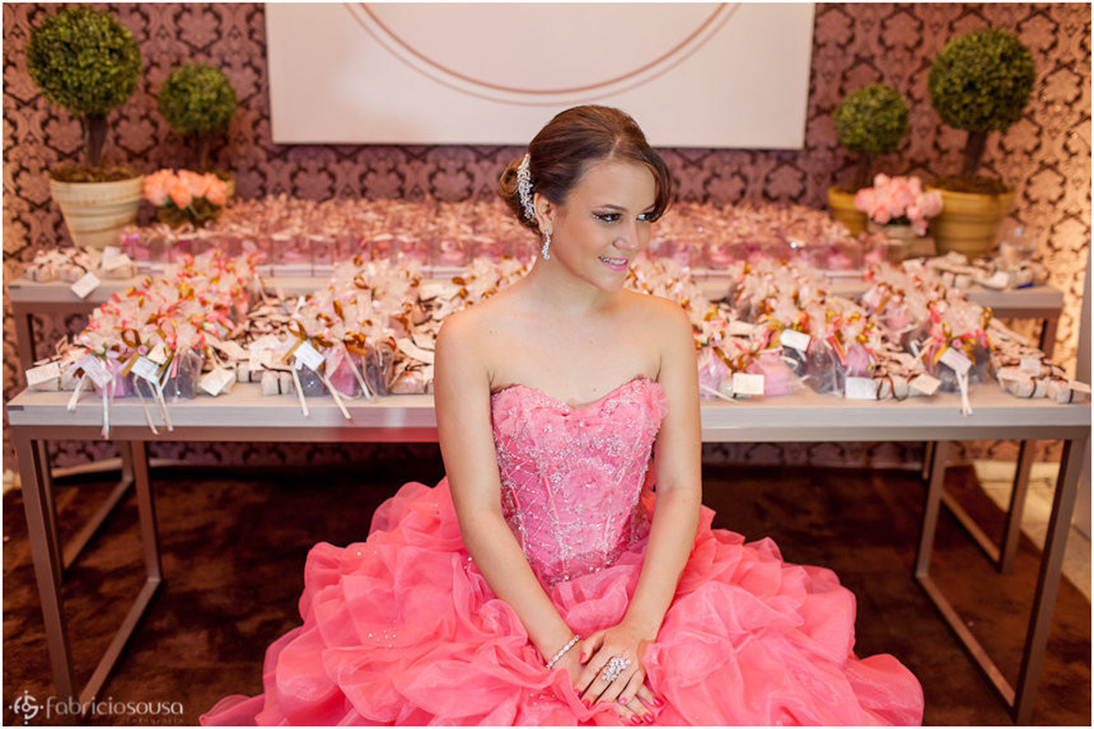 Debutante sentada em frente à mesa de doces
