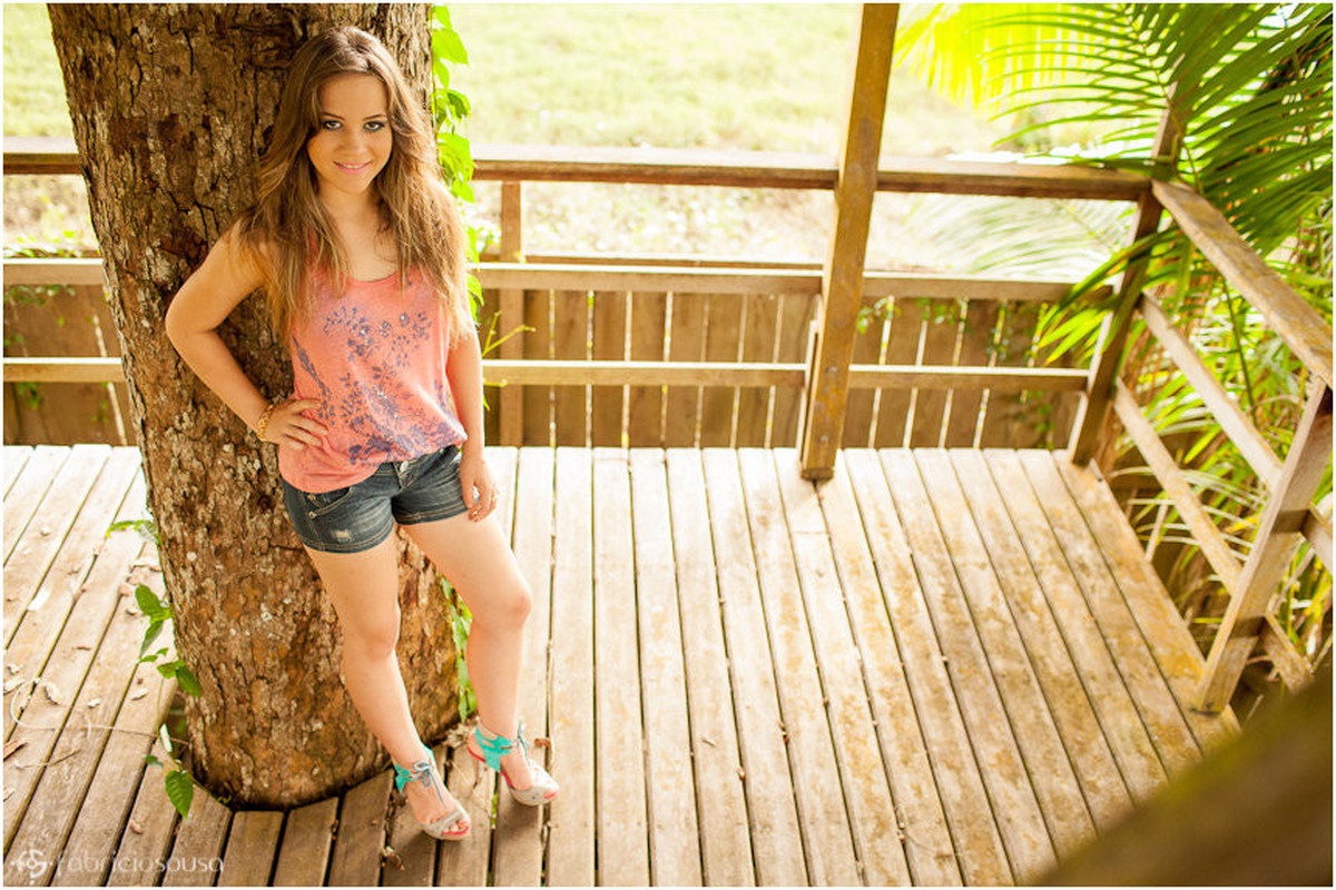 Késsia de blusa rosa e shorts se escora em árvore com mão na cintura