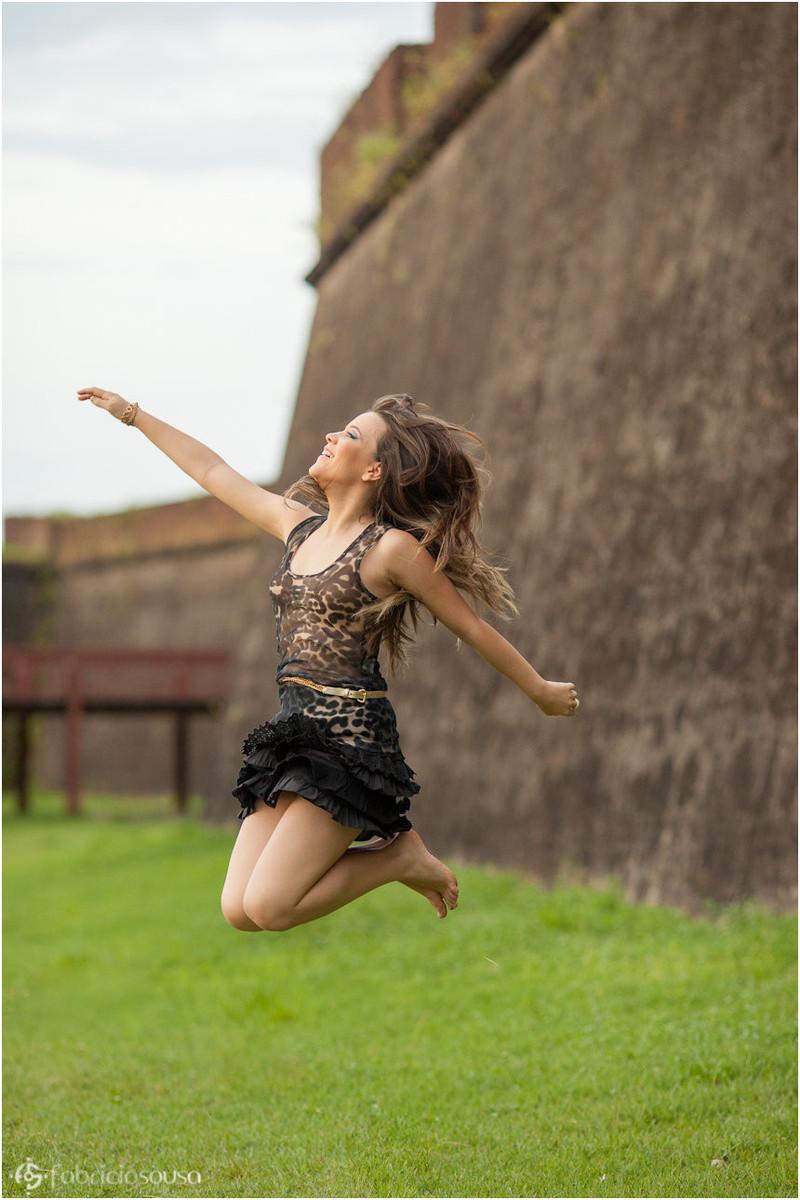 Jovem pula de alegria em frente do muro de pedra