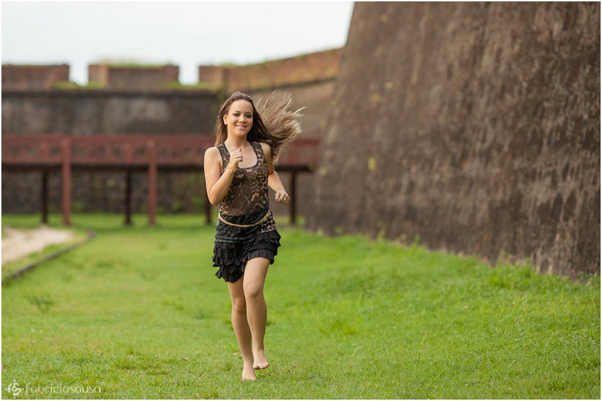 Ela corre no gramado em frente ao muro de pedra