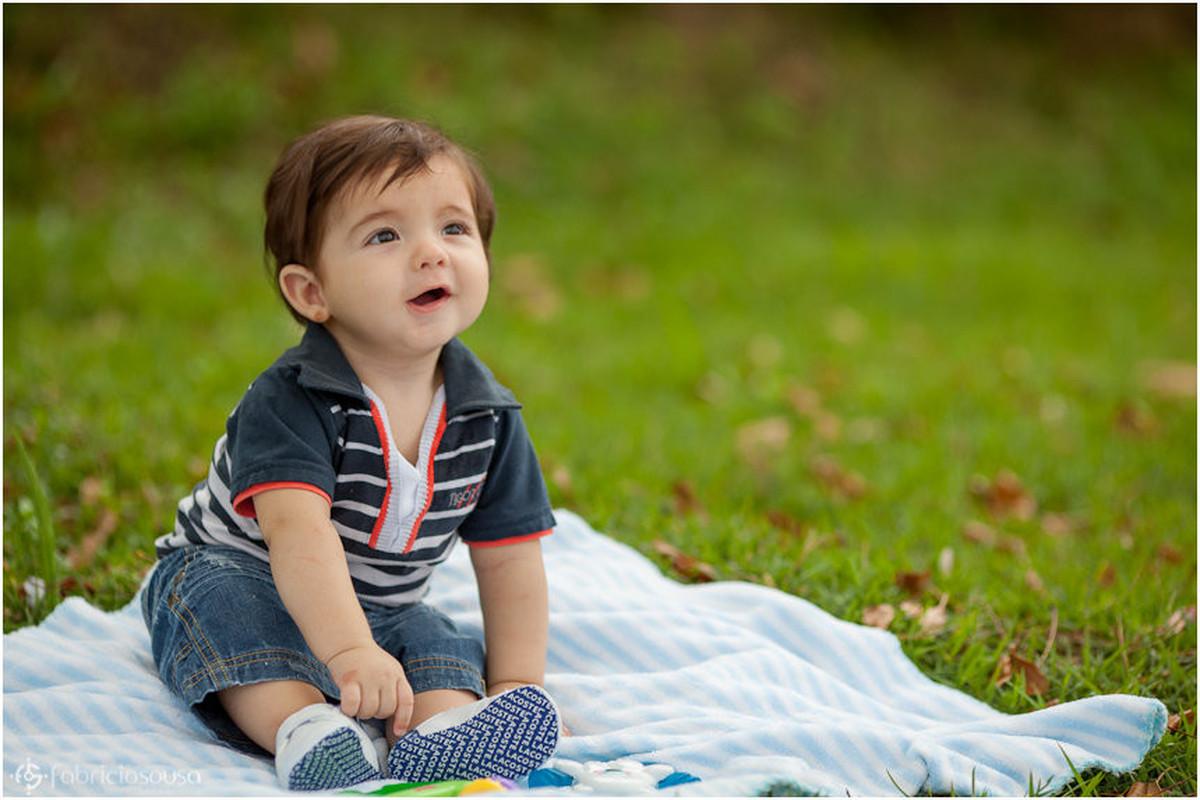 Lorenzo sentado sobre um lençol no gramado