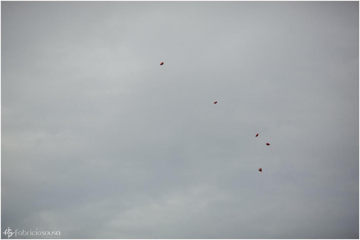 Balões vermelhos com formato de coração voam pelo céu
