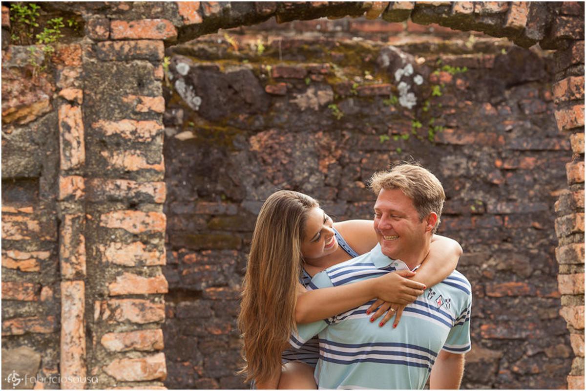 Troca de olhares em ensaio fotográfico familiar e muro de pedra