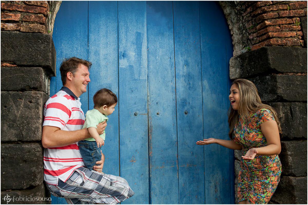 Família de 3 posam em frente à uma antiga porta azul de madeira