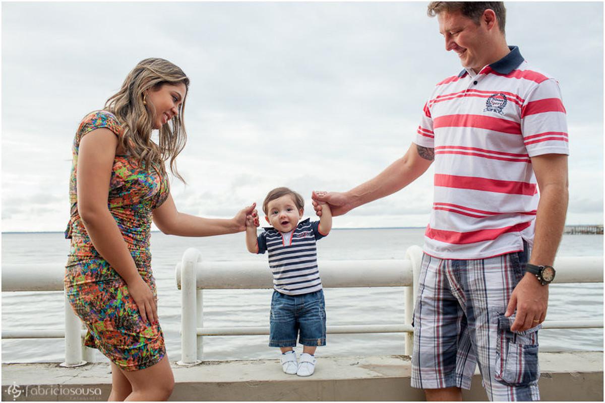 Mãe e pai seguram o braço do pequeno Lorenzo