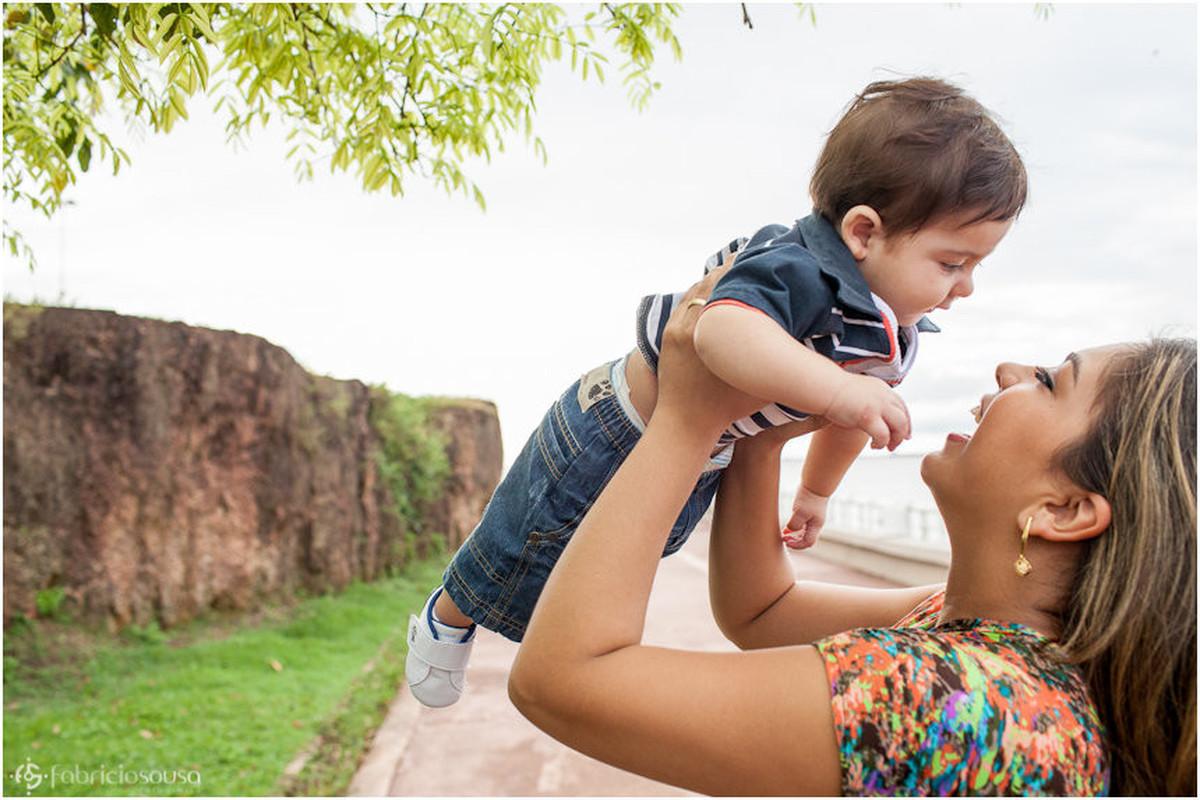 Mamãe alegre ergue o neném