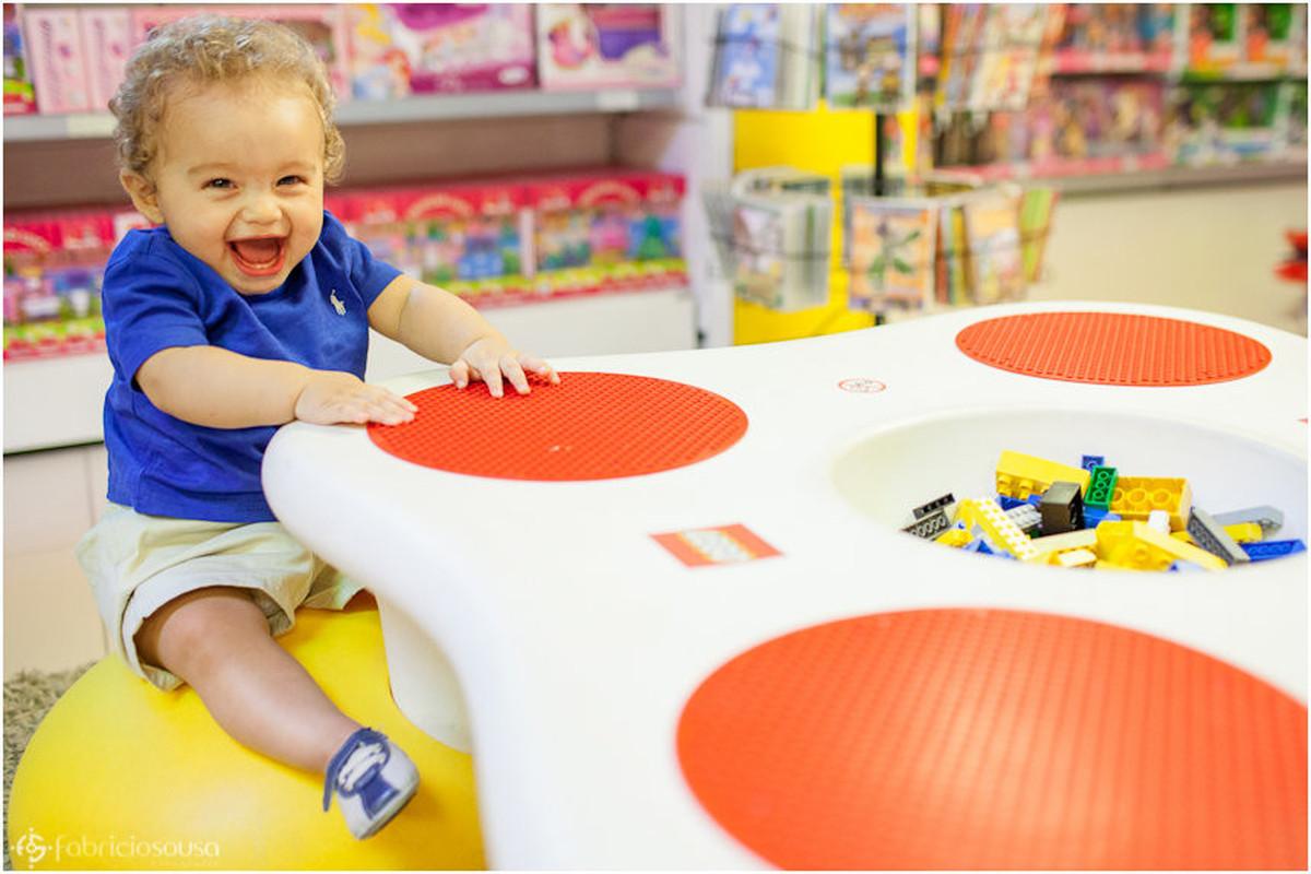 sessão infantil Vinícius sentando em mesa colorida