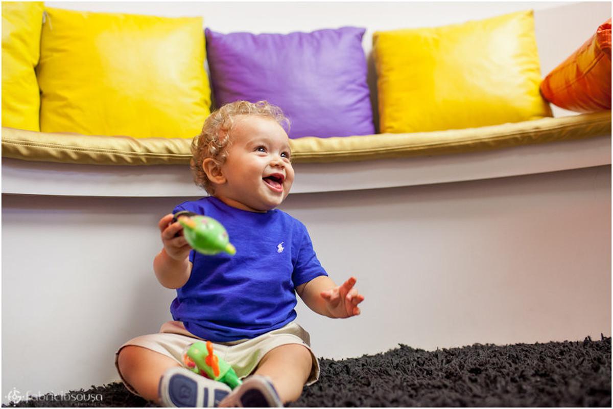 pequeno Vinicius super alegre com brinquedos e almofadas coloridas