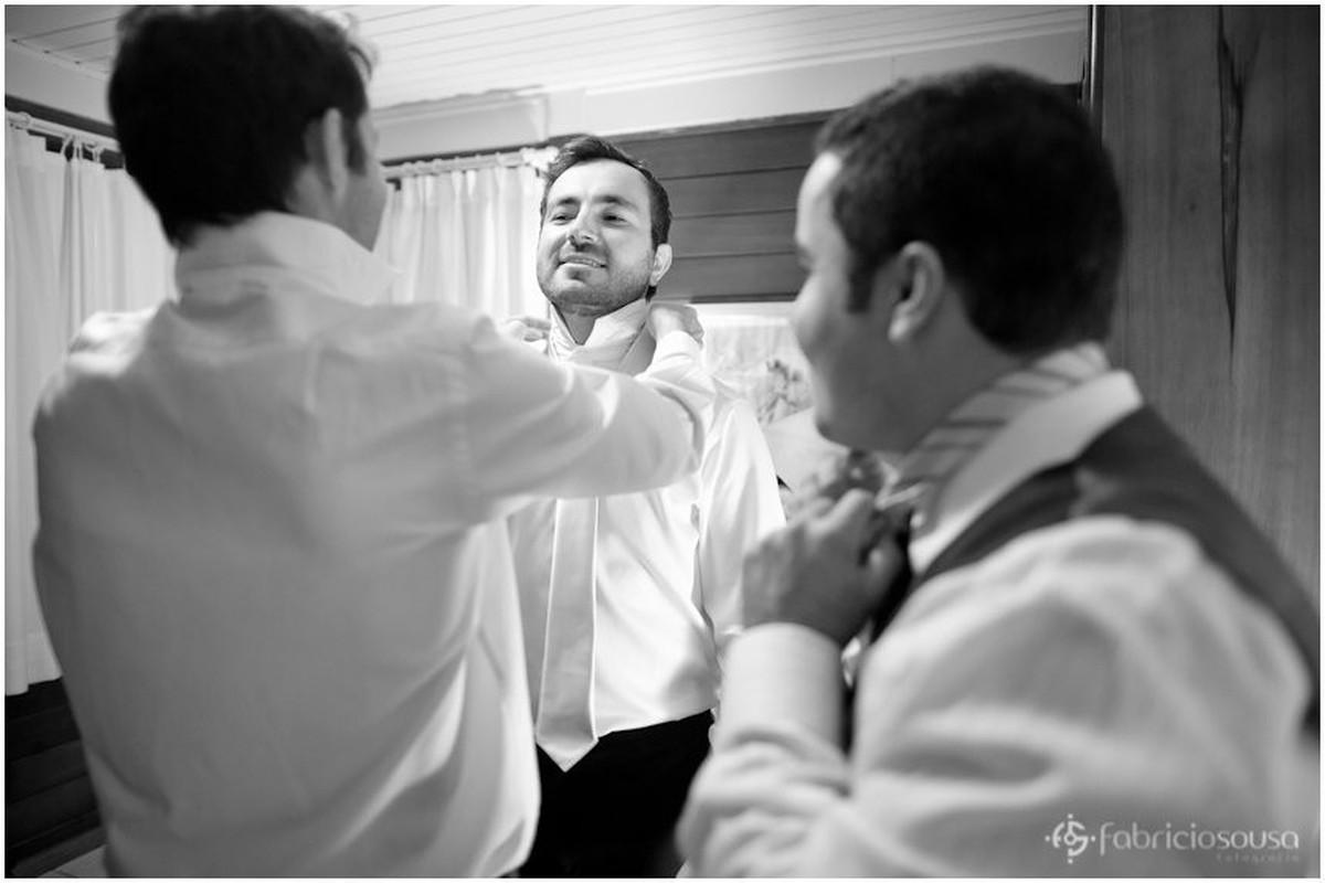 padrinho ajudando o noivo com o traje