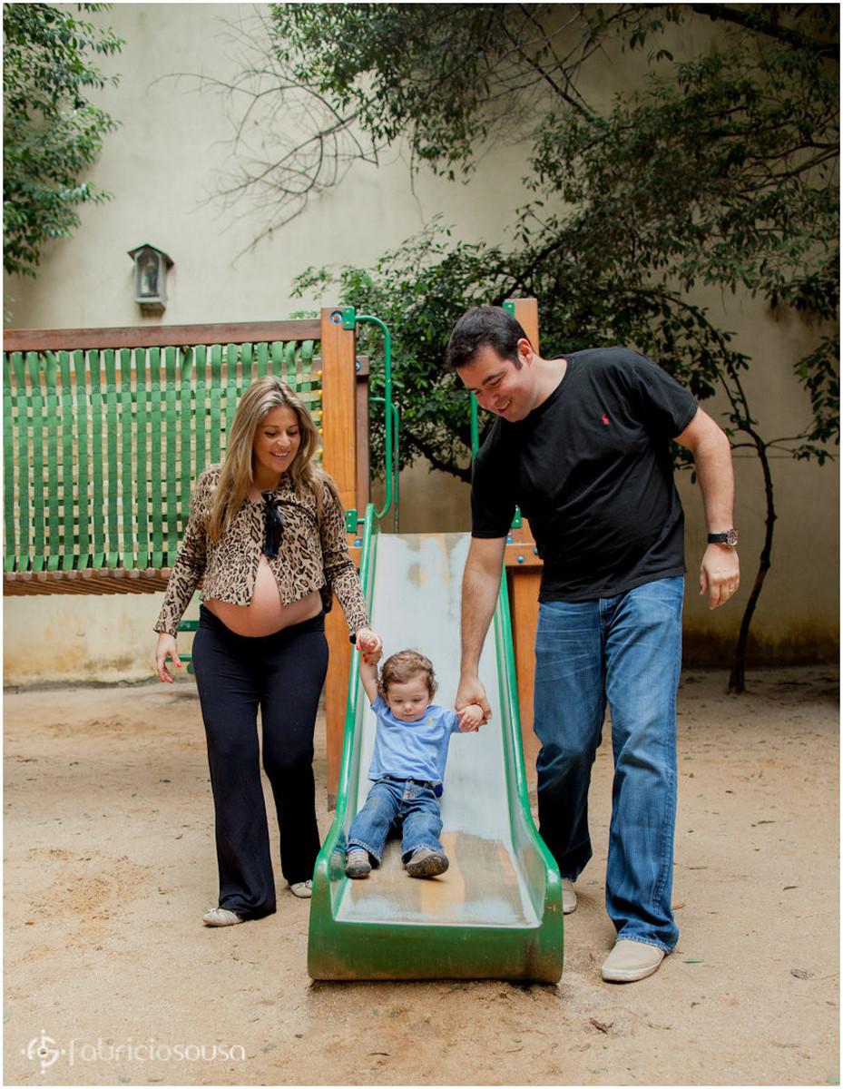 Família gestante brinca com filho pequeno no escorregador