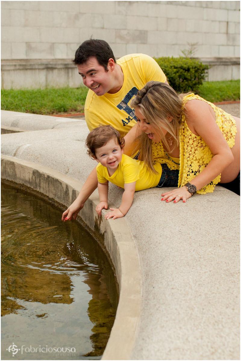 Mamãe e papai brincam com filho em fonte de água