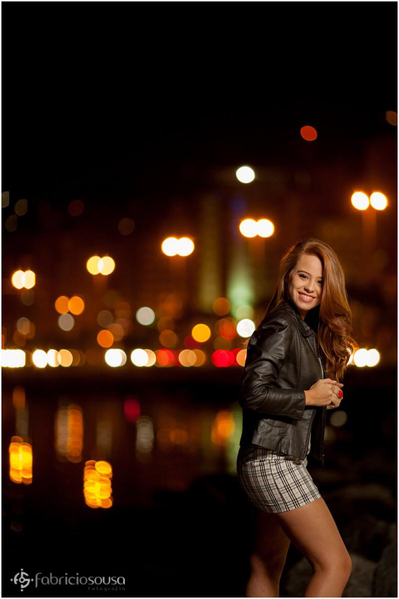 Nathalie sorridente com luzes da cidade ao fundo