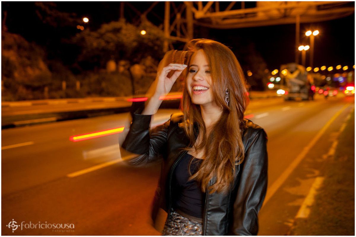 Nathalie sorri de jaqueta de couro próxima a ponte Hercílio Luz
