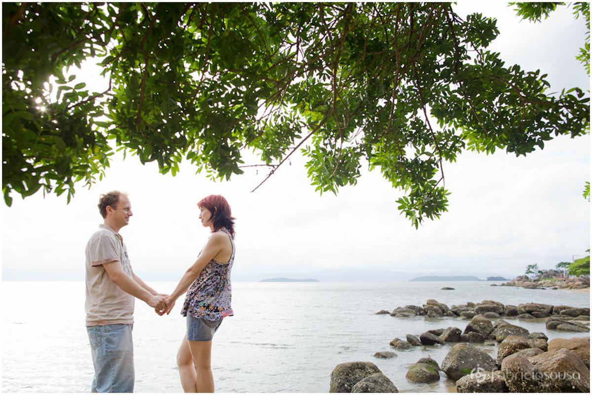 casal de mãos dadas com mar de Florianópolis de fundo