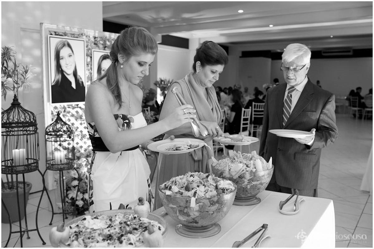 Formanda serve seu prato de jantar acompanhada dos pais