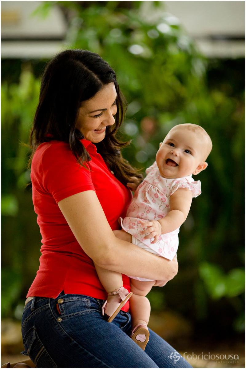 Mamãe com a filha risonha no colo