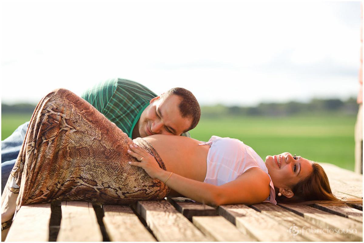 Pai escuta os movimentos do bebê dentro da barriga da mãe que está deitada no chão