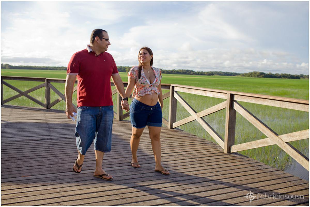 Homem e mulher gestante caminham sobre deck de madeira