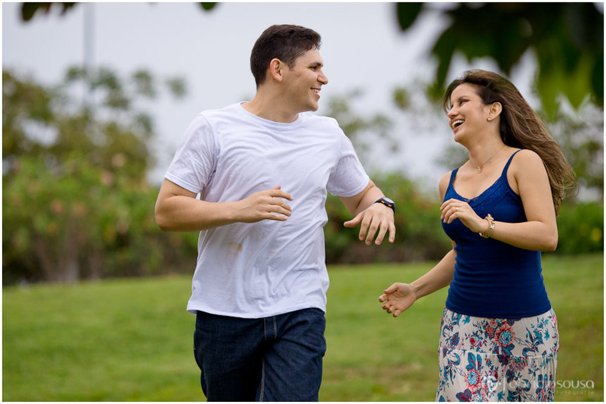 Casal corre sorridente pelo gramado