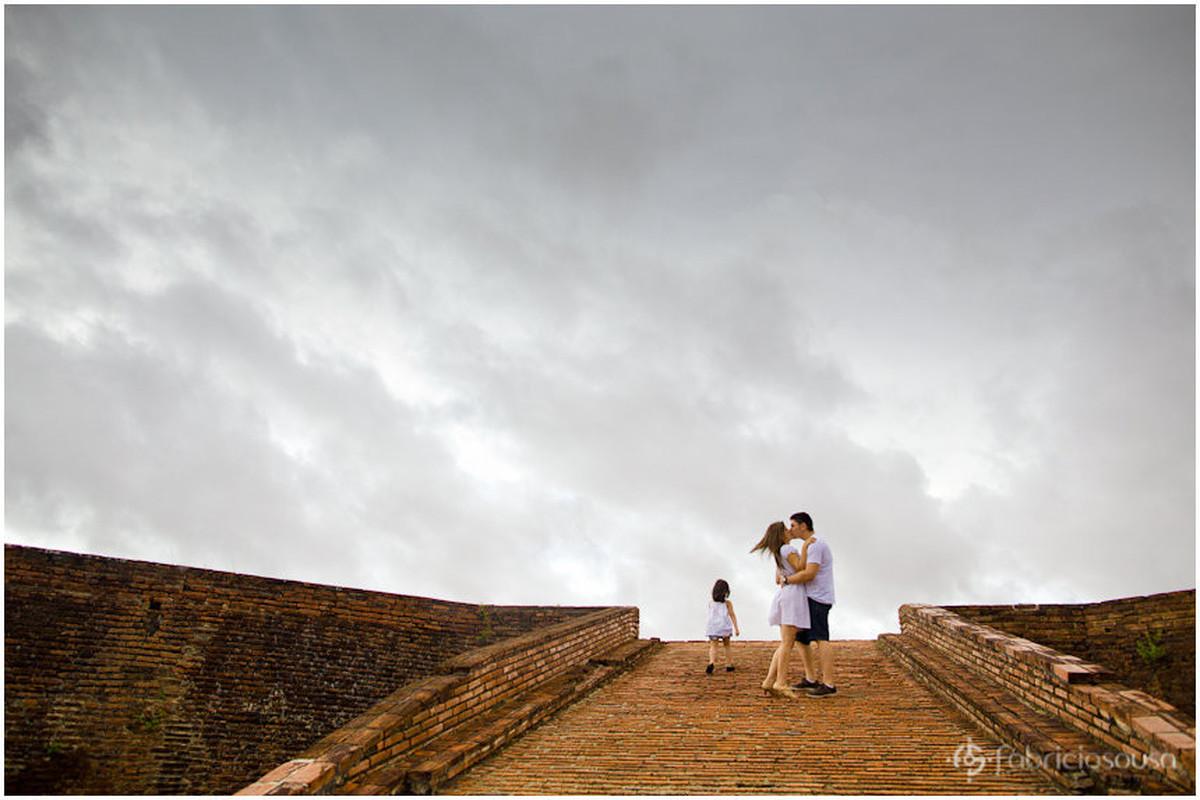 Beijo do casal e filha ao lado em rampa de tijolos e céu cinza